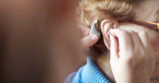 Audioprothésiste qui aide une personne âgée à choisir son appareil auditif