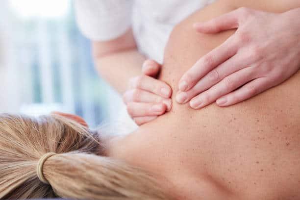 Ostéopathe qui effectue des palpations au niveau du dos de sa patiente pour soulager ses douleurs