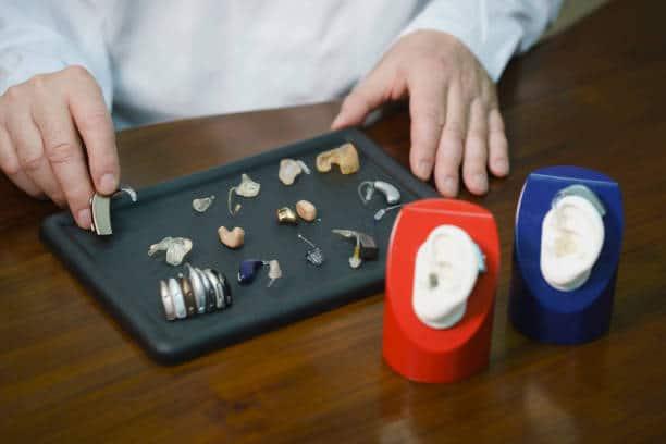 Audioprothésiste qui présente différents modèles d'appareils auditifs à son patient