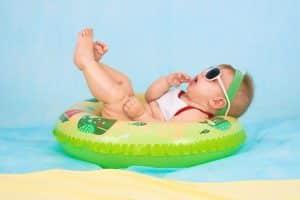 Bébé avec lunettes de soleil en train de flotter sur une bouée dans la piscine