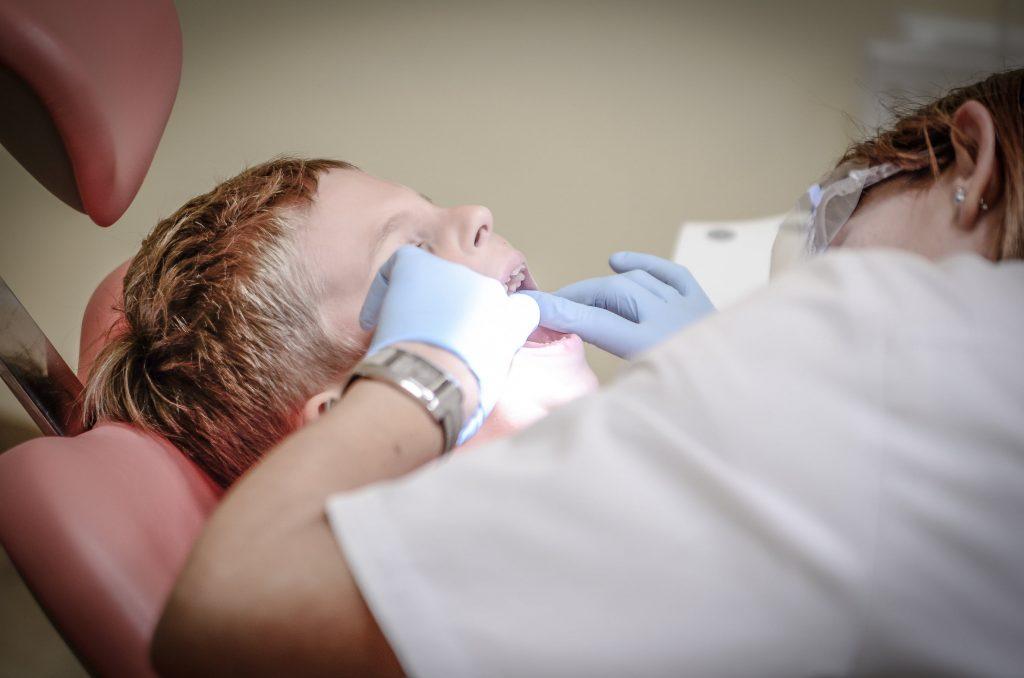Dentiste qui effectue des soins dentaires sur un enfant